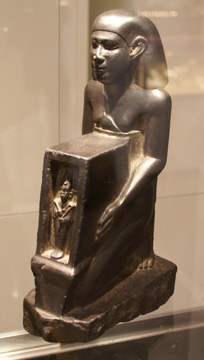 Egyptian basalt statue of man with naos with figure of Osiris