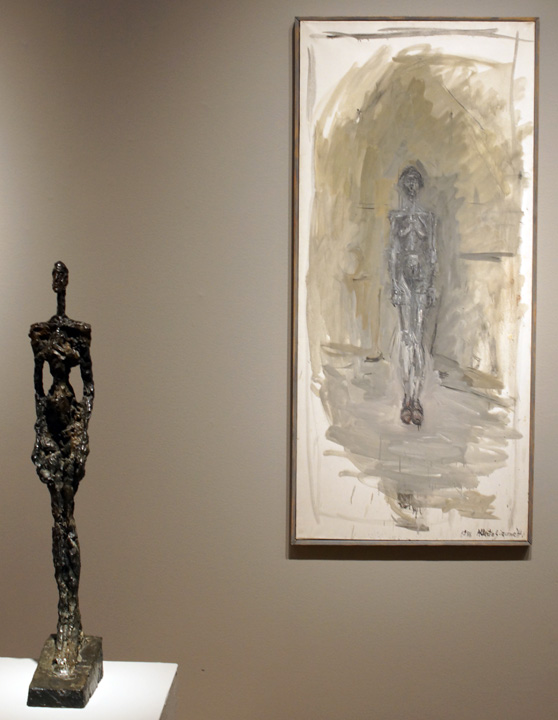 A sculpture of a man and a painting by Giacometti