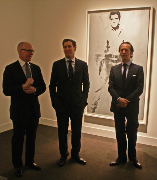 "Anthony Grant, Alex Rotter and Tobias Meyer of Sotheby's in front of Warhol's ""Elvis"""
