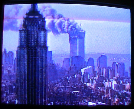 Television image of towers ablaza with Empire State building in foreground